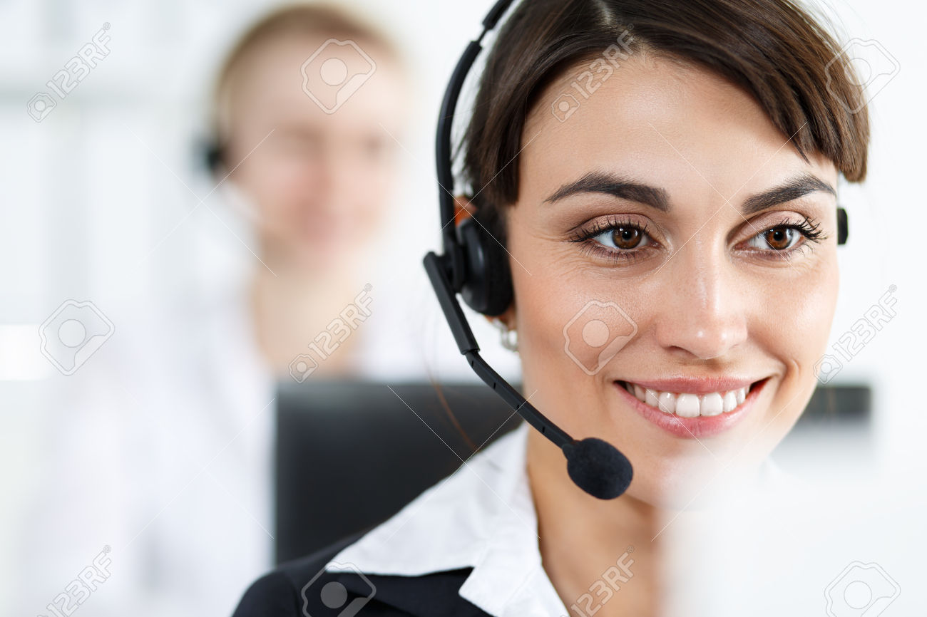 Female call center service operator at work. Portrait of smiling pretty female helpdesk employee with headset at workplace. Effective and efficient business information, help and support concept